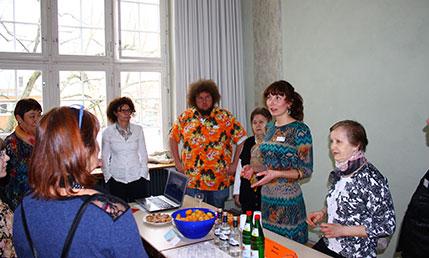 Zu sehen ist ein Tisch mit verschiedenen Speisen und Getränken, um den Tisch stehen Menschen im Gespräch, eine junge Frau erklärt, welche Speisen und Getränke für Weißrussland (Belarus) typisch sind.
