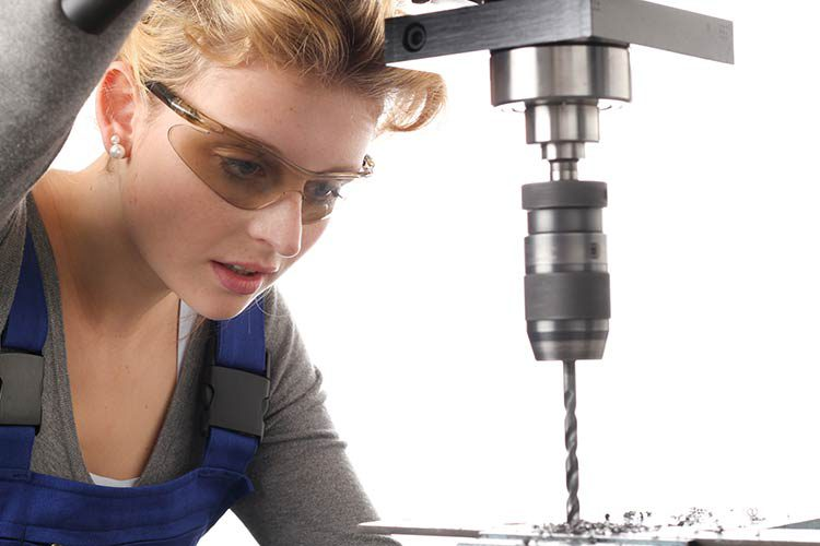 junge Frau mit Schutzbrille an Bohrmaschine
