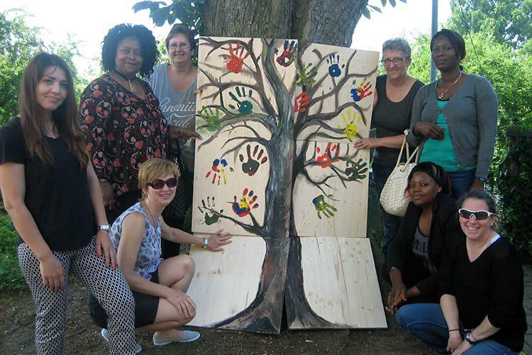 Gruppe junger Frauen vor einem Baum, zeigen ein selbstgemaltes Bild eines Baums