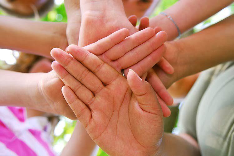 Kinderhände überdecken sich kreuzweise