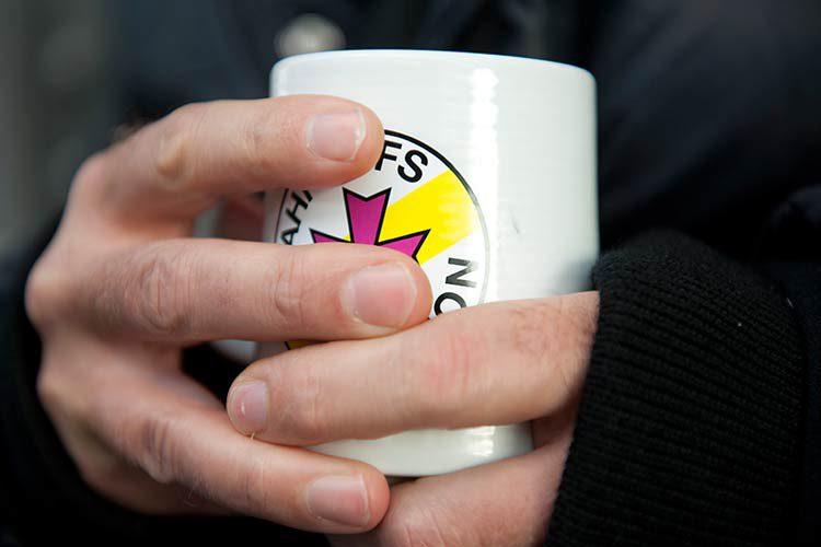 Hände umschließen eine Tasse mit dem Symbol Bahnhofsmission