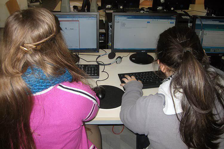 zwei jüngere Mädchen sitzen am PC