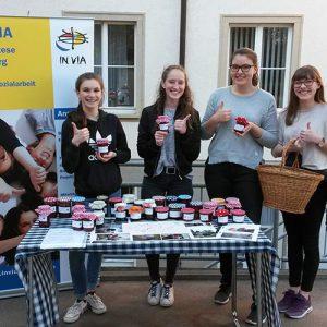 Schülerinnen am Stand der Schulsozialarbeit beim Tag der offenen Tür am Kolleg St. Sebastian in Stegen verkaufen selbstgemachte Marmelade