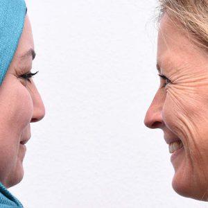Eine Muslima und eine blonde Frau schauen sich an