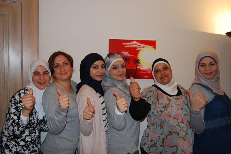 Fünf Frauen stehen vor einem Bild, Gesicht zur Betrachterin, Daumen hoch