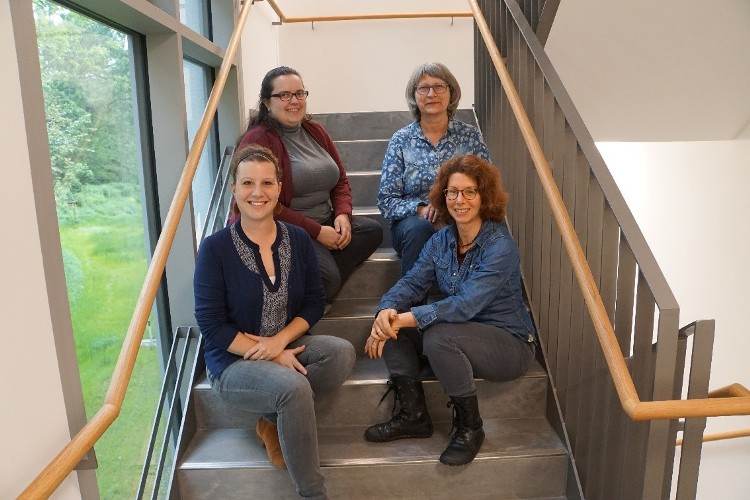 Foto von vier Damen der Mitarbeitendenvertretung, die auf einer Treppe sitzen